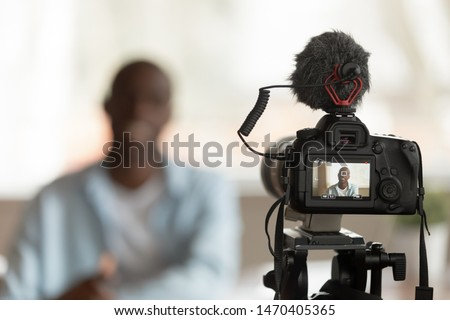 Close up professional camera filming young smiling african american speaker, professional trainer coach teacher, recording online course lecture presentation, commercial blogging or vlogging concept