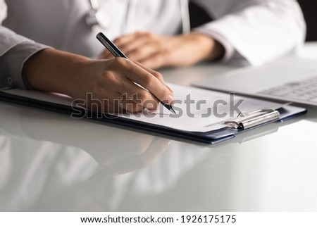 Close up professional female doctor wearing uniform taking notes in journal, physician therapist practitioner filling medical documents, clipboard, patient form, illness history, prescription