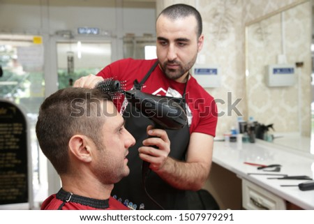 Close-up. Professional hairdresser makes styling client's hair using a hair dryer and a comb. Professional hairdresser tools on the table. Salon care. Concept for hairdressers and barbershop.