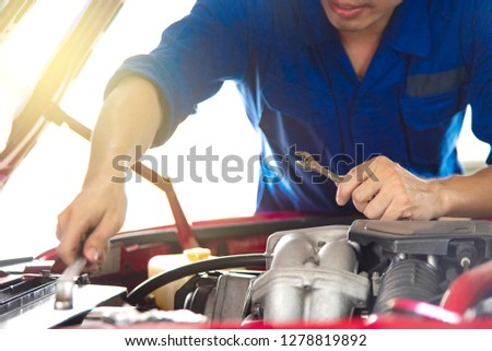 Close up professional technical engineer hand in blue uniform using tools to check something about engine in garage using for automobile industrial copy space with light and positive meaning