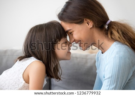 Close up profile faces smiling mother and daughter touching with foreheads with closing eyes. Mom expressing understanding candid emotions and love to sweet little child. Happy friendly family concept