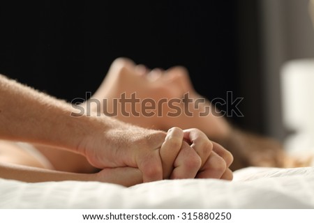 Close up profile of a couple having sex on a bed at home in the night