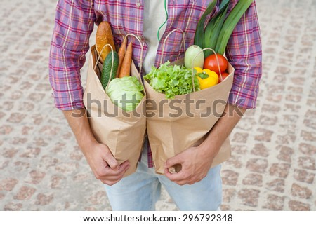 Close-up profile of bags full of fruits and vegetables. Young man carrying bags in his hands after shopping.