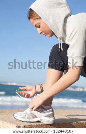 Close up profile portrait of a young sports woman doing up her trainers shoe laces against an intense blue sky by a golden beach.