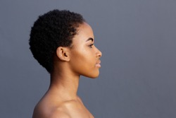 Close up profile portrait of african american young woman against gray background