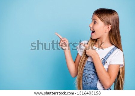 Close-up profile side portrait of her she nice cute attractive cheerful amazed glad straight-haired blonde girl pointing two fingers looking aside copy space isolated on blue pastel background