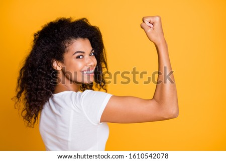 Close-up profile side view portrait of her she nice attractive lovely brunet cheerful wavy-haired girl showing strong muscles isolated over bright vivid shine vibrant yellow color background