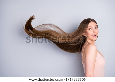 Close-up profile side view portrait of her she nice-looking attractive pretty cheerful well-groomed brown-haired girl wind blowing silky flawless hair isolated on light gray pastel color background