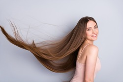 Close-up profile side view portrait of nice-looking attractive lovely gorgeous cheerful well-groomed brown-haired girl wind blowing silky smooth hair isolated on light gray pastel color background