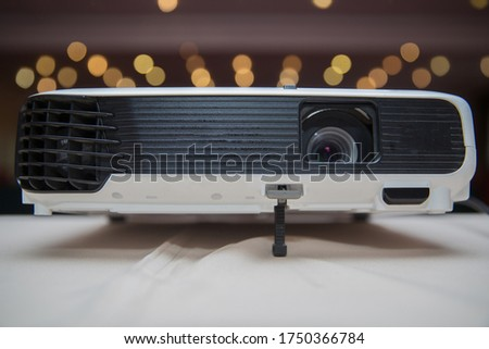 Close up projector in conference room . LCD Projector technology video presentation and home Entertainment object . mini led projector on wood table in a room projector home theater idea and concept