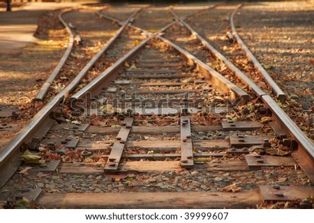 Close up railroad tracks switch with a fork going to the left and to the right