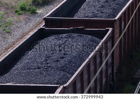 Close-up railroad tracks with wagons with coal on summer day