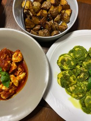 Close up Ravioli pasta in green Pesto served with oven toasted potato and cheese Tortellini in red meat sauce
