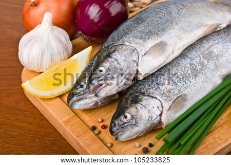 close-up raw fish trout with peppers, onions and lemon on a wooden board