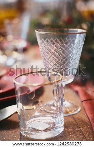Close up ready table christmas set with dishware glass and candle and xmas tree