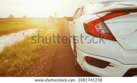 Close up rear of a car on the road with nature view