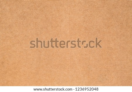 Close up rear side of brown plywood. Natural bumpy texture fiber material. Back view of compressed chipboard. Abstract dark background for wrapping paper, website template and greeting card backdrop.
