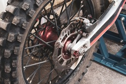 Close-up rear studded wheel of an enduro off-road motorcycle in garage on lift. Brake discs, chain, transmission. Photo of a cross bike part was taken from the side in the workshop.
