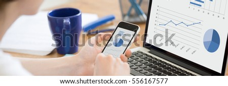 Close-up rear view of business woman working in office on pc holding smartphone and looking at screen with diagrams, using mobile phone and laptop. Horizontal photo banner for website header design