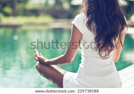 Close up Rear View of Slim Woman Meditating in a Lotus Yoga Position at the Poolside