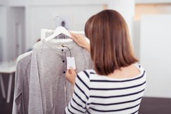 Close up Rear View of Woman Looking at the Price Tag of a Trendy Gray Shirt Hanged on Rail Inside the Clothing Store.