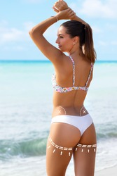 Close up rear view portrait of young woman in white bikini showing perfect muscular buttock. Brunette standing on beach with conceptual surgical dotted contour lines.
