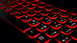 Close up. Red backlight, backlit on laptop or keyborad computer of gaming in the dark. Computer laptop keyboard with red dark backlight, backlit in the dark. Concept computer Thai keyboard background.
