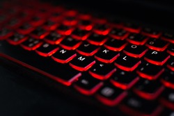 Close up. Red backlight, backlit on laptop or keyborad computer of gaming in the dark. Computer laptop keyboard with red dark backlight, backlit in the dark. Concept computer keyboard background.