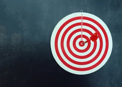 close up red dart arrow hitting on target center of dartboard, black copy space background for text, planning and manage to success business, good idea and creative, sport and relaxation concept