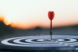Close up red dart arrow hitting target center dartboard on sunset background. Business targeting and focus concept.