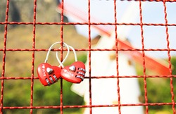 Close up Red heart-shaped lock padlock On the steel grate With a young couple in tourist attractions.