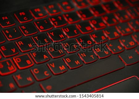 Close up red led backlit computer laptop keyboard keypad with dual alphabet, English and Cyrillic, high angle view #1543405814