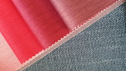 close up red tone fabric samples in  catalog book matching with green textile linen drapery fabric. combination of interior fabric samples for drapery or upholstery works.