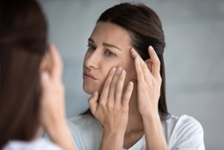 Close up reflection 35s woman touches face skin looks at mirror feeling worried about first wrinkles and age-related changes derma problems. Cosmetic facial plastic surgery skincare treatments concept