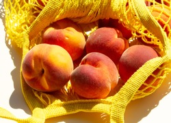 Close-up Ripe peaches in a mesh bag or string bag on light yellow background. Flat lay. Zero waste.