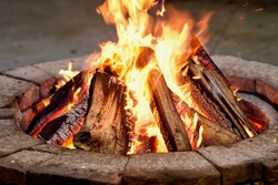 Close-up, roaring fire with blurred flames from wood logs in a stone firepit