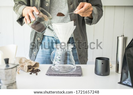 Close up. roasted coffee on a stainless spoon, with professional of barista pour Roasted coffee for dripping hot coffee into the cup with equipment, tool brewing at kitchen home