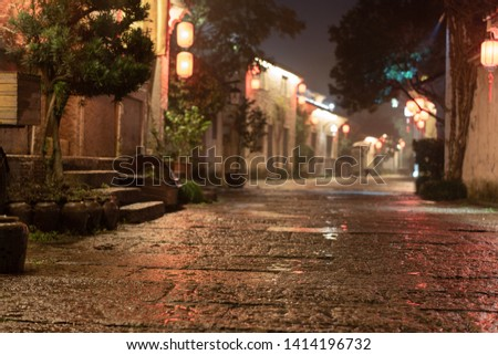 close up rock paved road of Chinese Ancient Town in the night. Rough surface with rain water. Defocused ancient building and tourists background. Low angle
