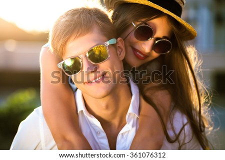 Close up romantic beauty portrait of happy hipster couple in love hugs and having fun, evening sunlight, stylish sunglasses, hat, emotions, joy, youth, sunny colors, hugs and kisses, vintage style.