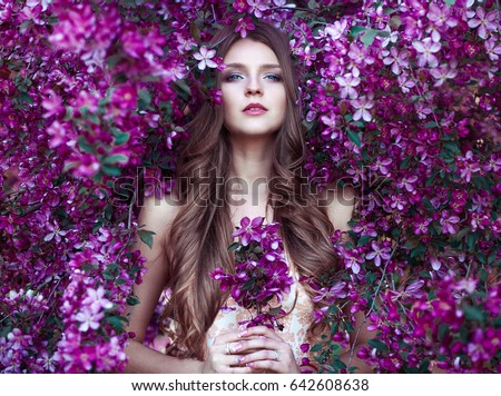 Close up romantic portrait of  beautiful elegant woman in blossom spring trees.