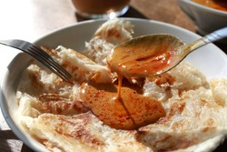 Close up Roti Parata or Roti canai with curry sauce. It is is an Indian-influenced flatbread dish, famous street food in Malaysia and Southeast Asia.