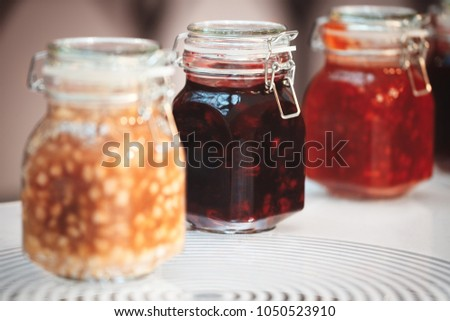 Close-up row of several glass with red yellow orange jars jam conserve confiture pozzy on table, breakfast concept, kitchen background, healthy eating concept, conservation concept. #1050523910