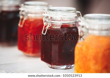 Close-up row of several glass with red yellow orange jars jam conserve confiture pozzy on table, breakfast concept, kitchen background, healthy eating concept, conservation concept. #1050523913