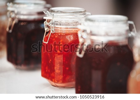 Close-up row of several glass with red yellow orange jars jam conserve confiture pozzy on table, breakfast concept, kitchen background, healthy eating concept, conservation concept. #1050523916