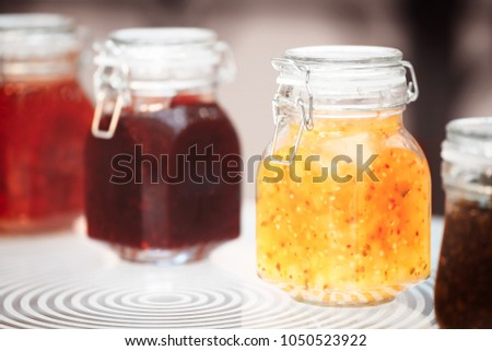 Close-up row of several glass with red yellow orange jars jam conserve confiture pozzy on table, breakfast concept, kitchen background, healthy eating concept, conservation concept. #1050523922