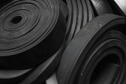 Close-up rubber sealing strips for waterproof doors. A pile of rubber twisted into rolls.