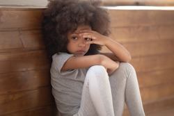 Close up sad african girl seated on floor feels lonely, mixed-race kid lost in sad thoughts need psychological support help of counsellor, racial discrimination no friends, developmental delay concept