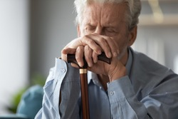 Close up sad tired older man holding hands on walking stick, problem with health, upset unhappy mature senior male using wooden cane during rehabilitation, elderly people healthcare
