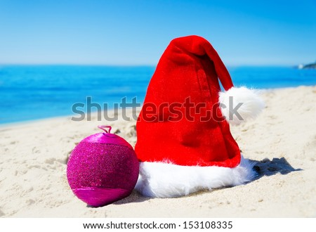 Close up Santa hat with ball on the beach by the ocean - Christmas and New Year concept #153108335