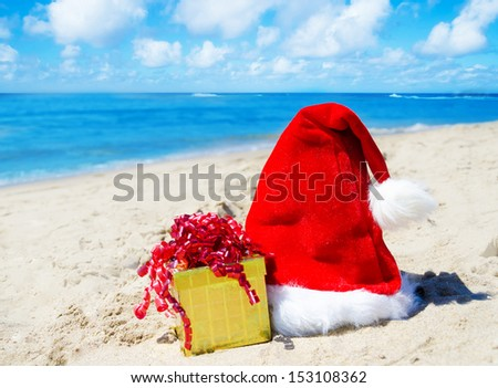 Close up Santa hat with gift box on the beach by the ocean - holiday concept #153108362
